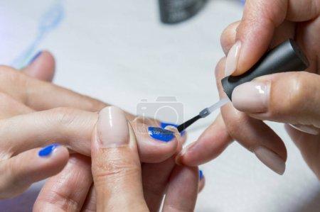 Photo pour Manucure. Application de vernis à ongles, vernis à gel bleu. - image libre de droit