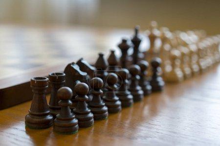 Photo pour Chess pieces in front of chessboard. - image libre de droit