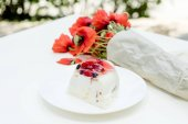 Tasty sweet fruit pie and bouquet of poppy red flowers on white table