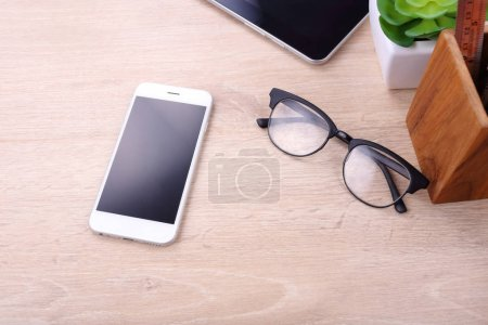 Blank screen smartphone and office supplies on wooden background