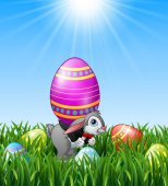 Cartoon easter bunny carrying easter eggs in the grass background