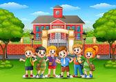 Happy school children standing in front of school building