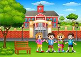 Happy school children standing in outside the front of school building