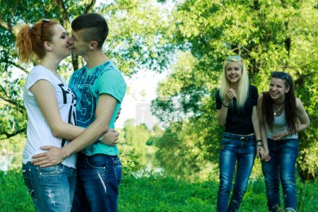 teenagers laugh at the pair of girl and boy lovers kissing outside