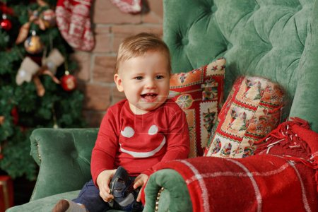 Little boy with chubby cheeks smiles at Christmas. The interior