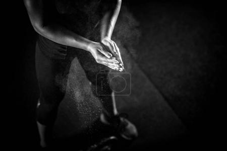 Woman athlete putting weightlifting chalk