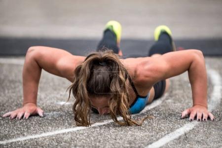 Woman doing pushups outdoors