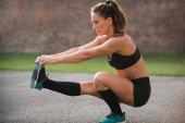 Sportswoman stretching leg, balancing