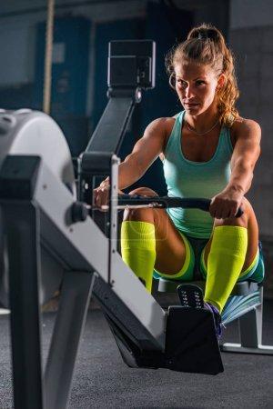 Woman athlete exercising on rowing machine