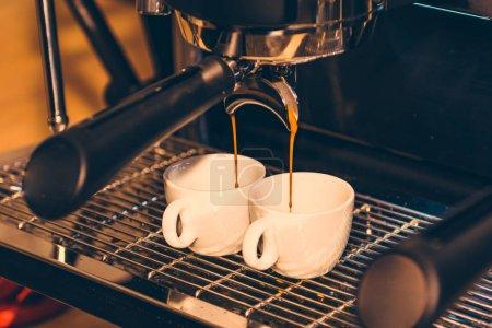 Italian espresso coffee machine and two coffee cups