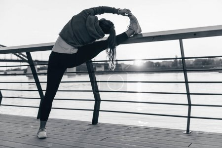 Woman streching by the riverside in the city at the sunset
