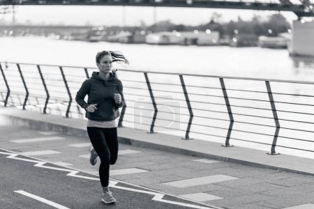 Photo pour Jeune femme jogging dans la ville - image libre de droit