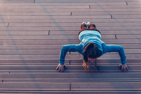 Woman doing push-ups on stairs