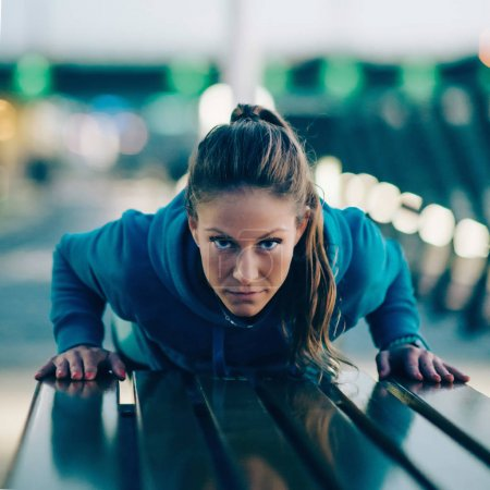 young woman doing Push ups on bench