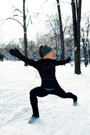 Female athlete exercising in park in winter with snow around the park. Listening music and exercising