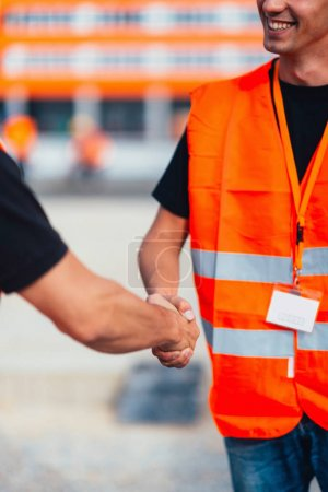 Construction workers handshaking on construction site