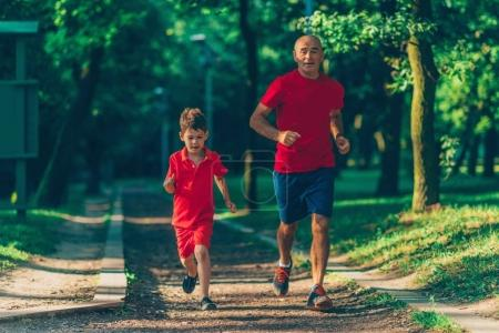 Photo for Grandfather and grandson jogging in park - Royalty Free Image