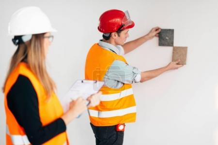 Engineers examining tiles on construction site
