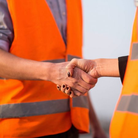 Architects handshaking after successful meeting on construction site