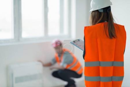 Maintenance Engineer checking air conditioner while woman checking list