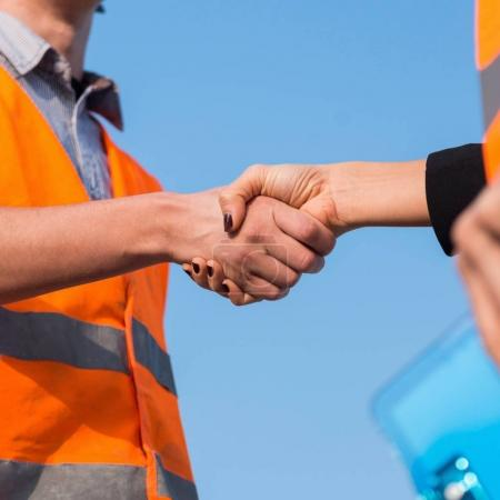 Civil engineers handshaking on construction site after successful meeting