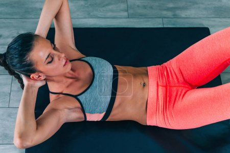 Young woman exercising in the gym. Doing sit-ups