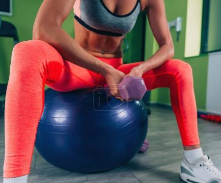 Young woman exercising  on pilates ball with weights in the gym