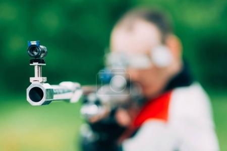 Man on free rifle triaing outdoors