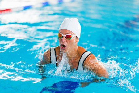 Female swimmer on training in the swimming pool. Breaststroke swimming style