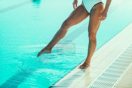 Female swimmer on poolside, close up of legs