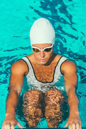Female swimmer in the pool in cap and goggles
