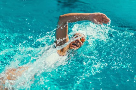 Female swimmer on training in the swimming pool. Front crawl swimming style