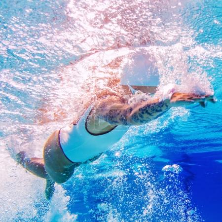 Female swimmer with tattoos. Underwater shoot