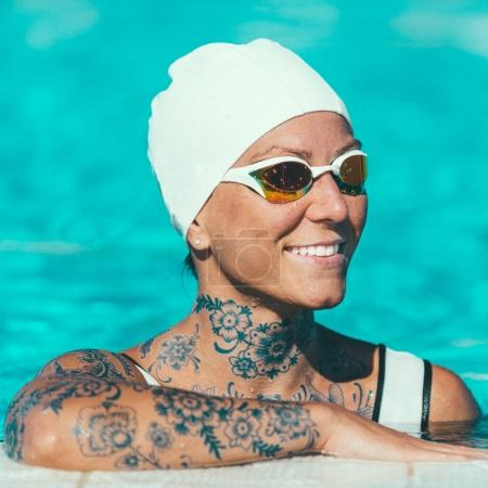 Portrait of female swimmer with tattoos  in the cap