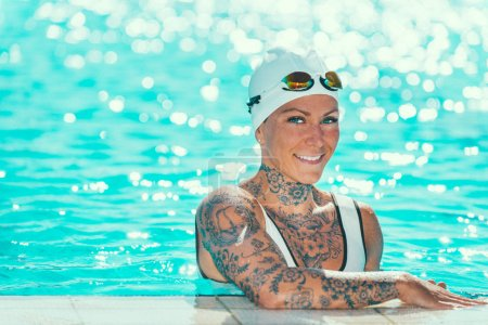 Portrait of female swimmer with tattoos on pool edge