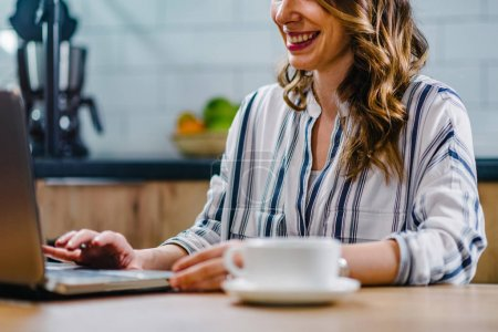 Young woman  holding coffee and working on laptop at home