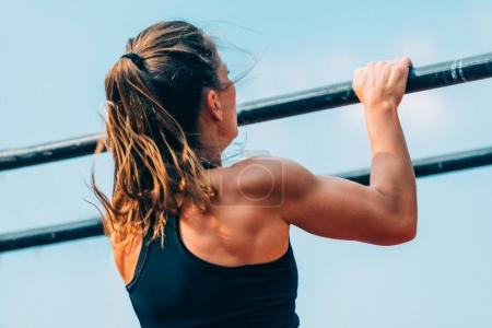 Female doing pull ups on crossfit competition