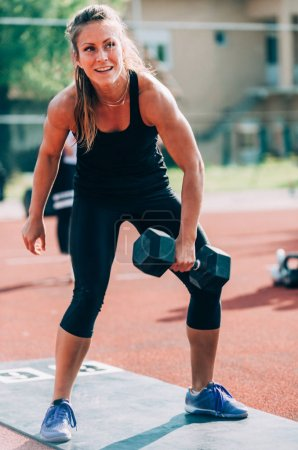 Woman with weights on crossfit competition