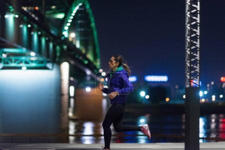 Photo pour Femme au jogging tard dans la nuit à l'extérieur - image libre de droit