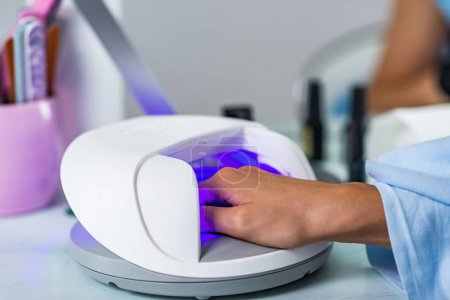 close up of Manicure treatment with woman hand in  Ultraviolet lamp