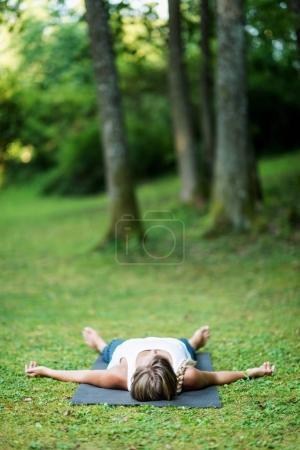 Photo for Girl doing yoga, meditating, Shavasana or corpse position - Royalty Free Image
