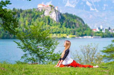 Woman doing yoga by the lake
