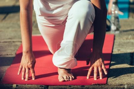 woman doing High lunge yoga pose on yoga event.  Detail on arms and feet