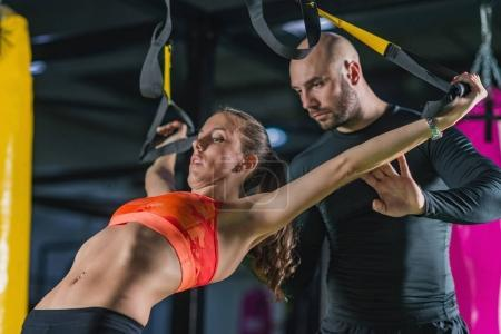 Personal trainer exercising on TRX with woman in the gym