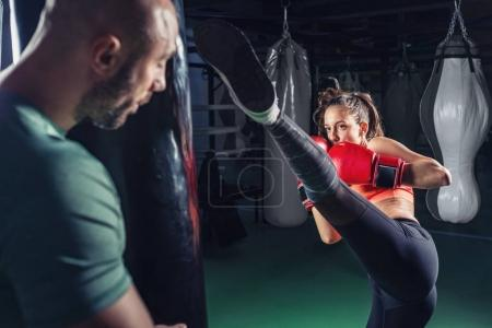 Female on boxing with her male instructor