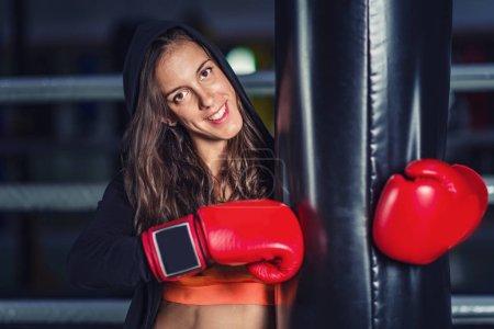 Photo pour Femme en entraînement de boxe avec sac de boxe - image libre de droit