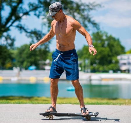 Active senior man riding a snakeboard by the lake
