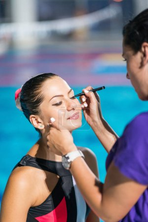 trainer Applaying make up before competition on synchronized swimming competition