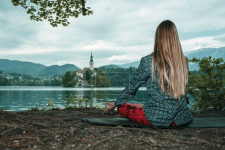 woman doing Mindful meditation by the lake