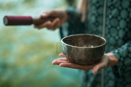 woman holding Tibetan singing bowl